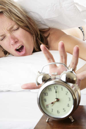 Woman waking up late and reaching for her alarm clock photo