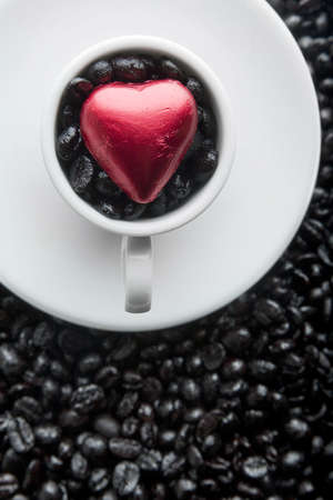 Coffee cup with black beans and red heart photo