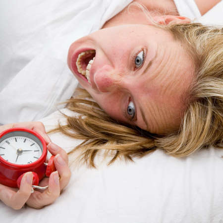 Woman with red alarm clock representing lateness or a deadline photo