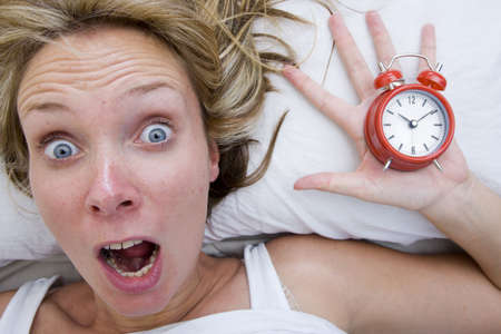 early morning: Woman with red alarm clock representing lateness or a deadline