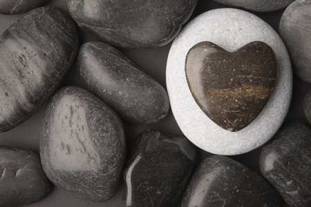 Heart shaped pebble framed on a dark pebble background Stock Photo