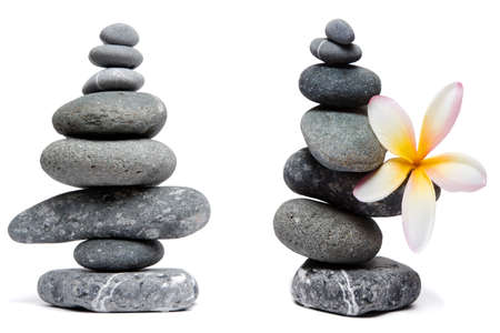peeble: Two nicely balanced pebble stacks, one with a frangipani or plumeria flower, isolated on white