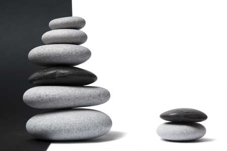 balanced: Black and white pebbles arranged in stacks with nice balance and a split black and white background Stock Photo