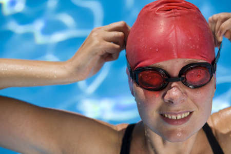 Athletic woman in swimming gear with blue swimming pool photo