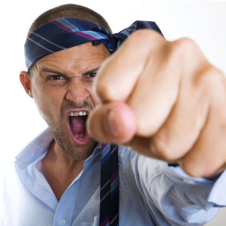 A very angry businessman waving his fist at the viewer photo