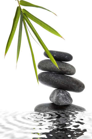 Stack of lave pebbles with bamboo leaves and a water reflection photo