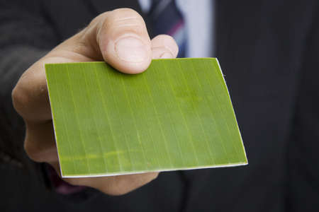 Man giving out a green business card