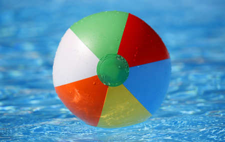 Dead centred shot from a low angle of a floating beachball in a bright blue pool photo
