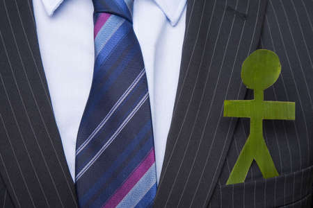 Man in a business suit with a little green man in his pocket photo