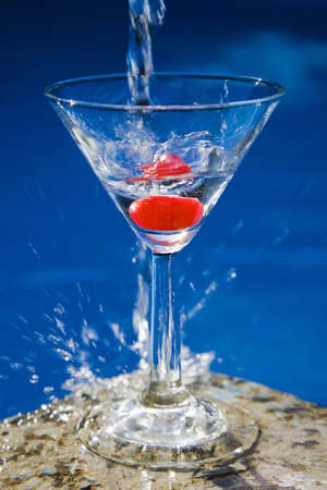 Martini with a cherry in front of a nice blue pool with a splash of water Stock Photo - 5824853
