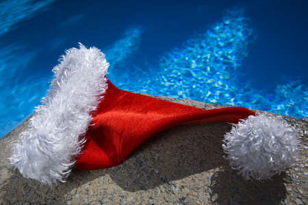 Nice santa hat by a blue swimming pool
