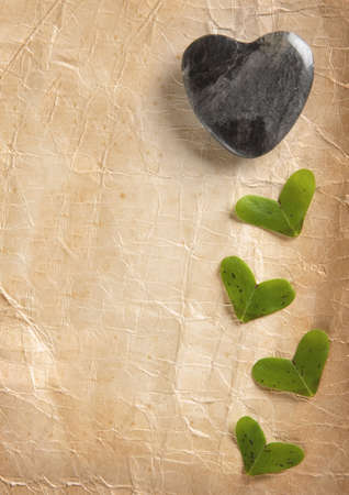Stone Heart and little heart shaped leaves on old foxed paper Stock Photo