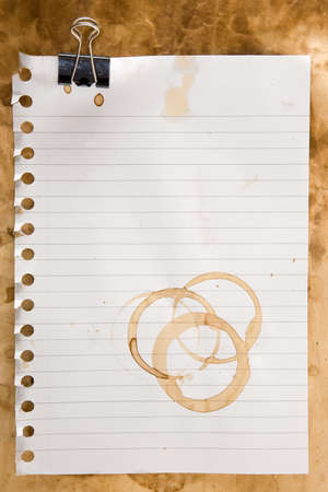 stain: Paper from a notepad with coffee stains and clip