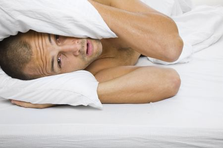 disturbed: Man trying to sleep with a pillow over his head