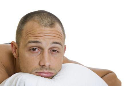 insomnio: Hombre en la cama tratando de dormir con una almohada