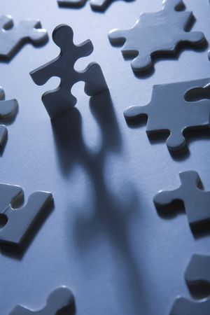Backlit jigsaw puzzle pieces with one standing up and looking anthropomorphic photo