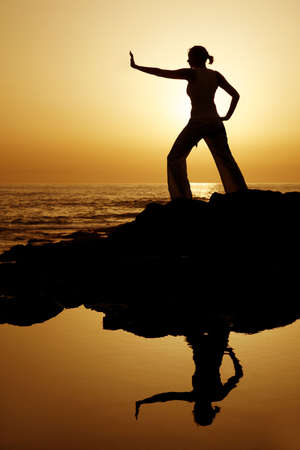 Yoga woman silhouetted against the setting sun with a natural reflection in a rockpool photo
