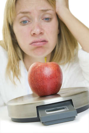 Diet concept with an apple on scales and a fed up woman behind photo