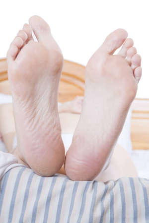 A womans feet at the end of a bed with a striped duvet photo