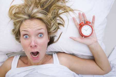 oversleep: Woman in bed realizing that she has slept in despite having an alarm clock