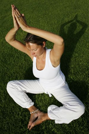 Woman in white in yoga position with green background
