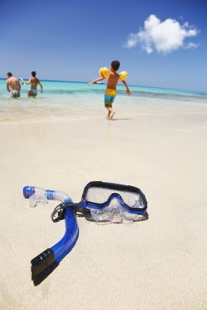 Boy running past snorkel on a tropical beach