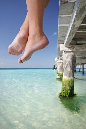 pies sexis: Uno de una serie grande. Gran sistema de piernas que cuelgan sobre el borde de un embarcadero tropical.