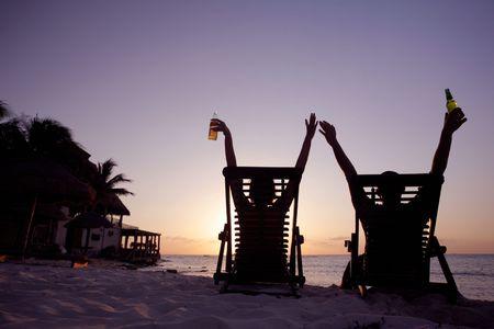 hombre tomando cerveza: La pareja se extiende a la puesta de sol en tumbonas