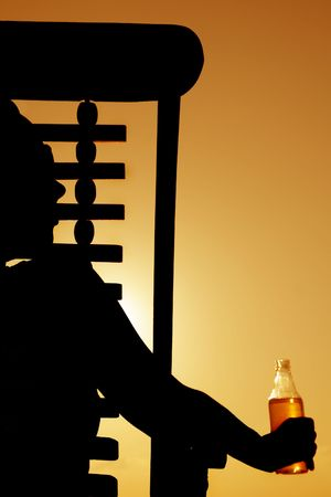 seeting: Woman drinking beer in a deckchair at sunset Stock Photo