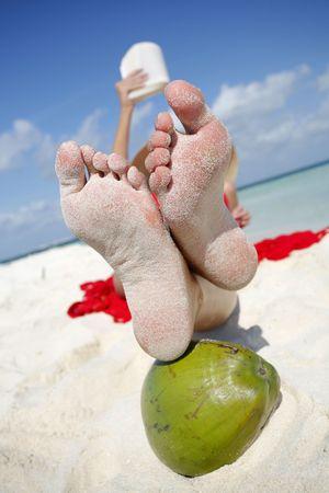 sandy: Mujer lectura en la playa con su feeton un �rea verde de coco.  Foto de archivo