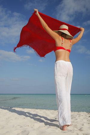 shaking out: Woman shaking out a saong on a tropical beach Stock Photo
