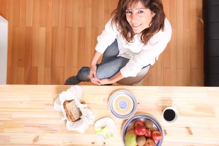 Portrait of a beautiful mature woman sitting in the kitchen. photo