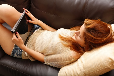 A young woman holding a Tablet PC while relaxing on the sofa. Stock Photo