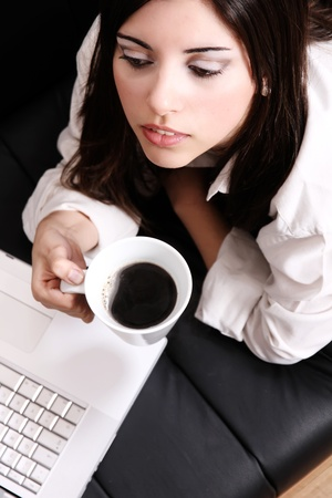 A young, hispanic adult girl watching a Laptop while drinking coffee  Stock Photo - 21552183