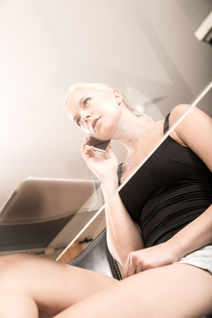 A Girl sitting at a glass desk on the phone Stock Photo - 21723689