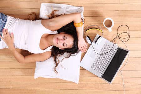 perezoso: Una joven tendido en el suelo despu?s de navegar por Internet con un ordenador port?til.