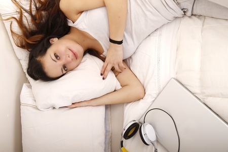 A young adult Woman relaxing on the Bed with a Laptop and Headphones.. photo