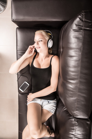 A blonde girl with Headphones laying on the sofa. photo