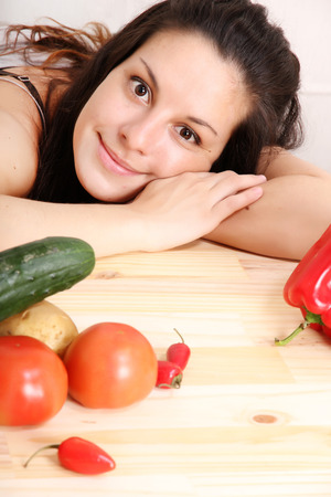 A young hispanic girl in the kitchen between vegetables. photo