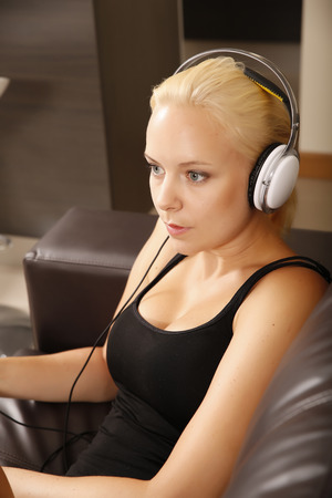 A blonde girl with Headphones and a smartphone sitting on the sofa. Stock Photo - 22497203