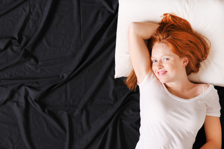 lazyness: A young adult Woman lying on bed, smiling.  Stock Photo
