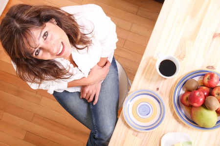 Portrait of a beautiful mature woman sitting in the kitchen. Focus on the Face. photo