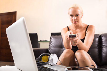 A blonde girl watching TV with the remote control in her hands  photo