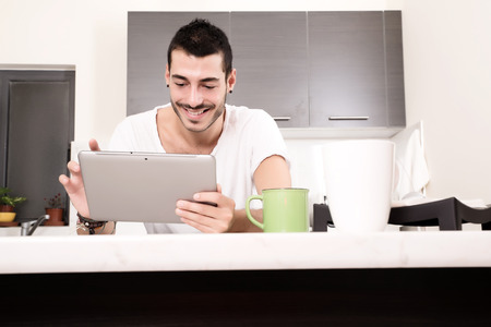 A young male sitting in the kitchen with a Tablet PC. photo