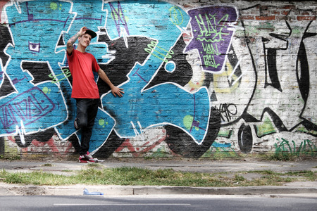 A greeting young Rapper greeting in front of a Graffiti wall. photo