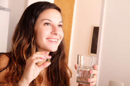 hand holding pills: A young woman taking a pill with a glass of water.