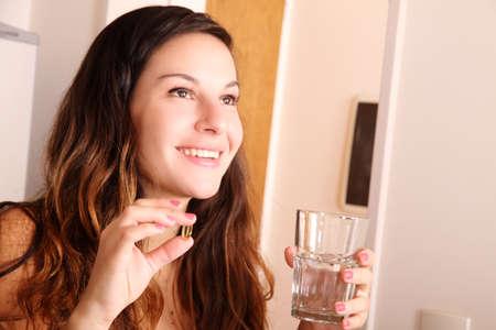 personas tomando agua: Una joven mujer tomando una pastilla con un vaso de agua.