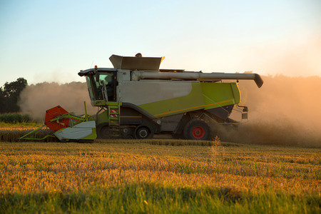 A field getting harvested by a agricultural machine. photo