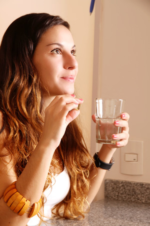 A young woman taking a pill with a glass of water. photo