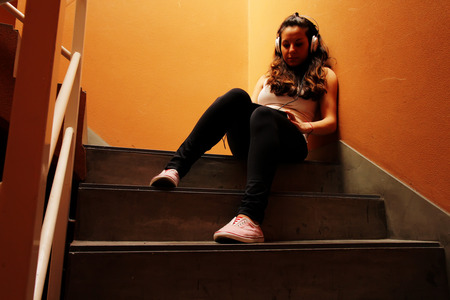 melancholic: A young woman listening to melancholic Music sitting in the stairway. Stock Photo